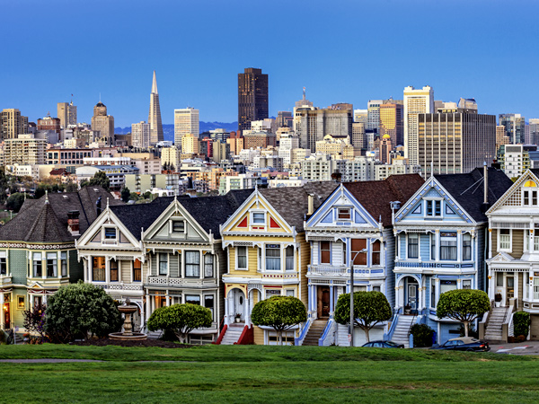 Image of San Francisco showing brightly painted homes in the foreground and the downtown skyline in the background.
