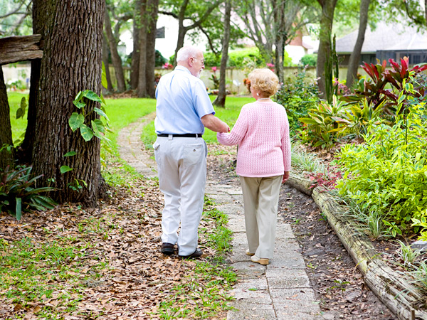 An elderly couple holding hands walking outdoors.