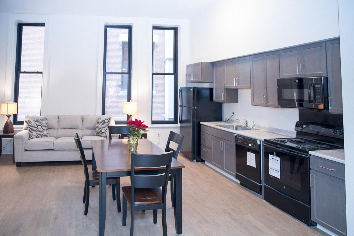 Image of an apartment interior furnished with a kitchen table, oven, dishwasher, refrigerator, and sofa.