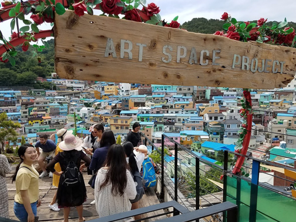 "People stand on a wooden deck enclosed by a metal railing overlooking homes. A sign stating, ""Art Space Project,"" is visible in the foreground."