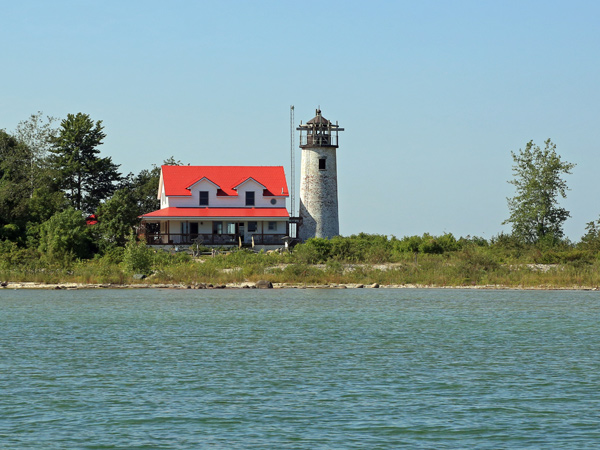 Image of a house and a lighthouse along Lake Huron's Saginaw Bay.